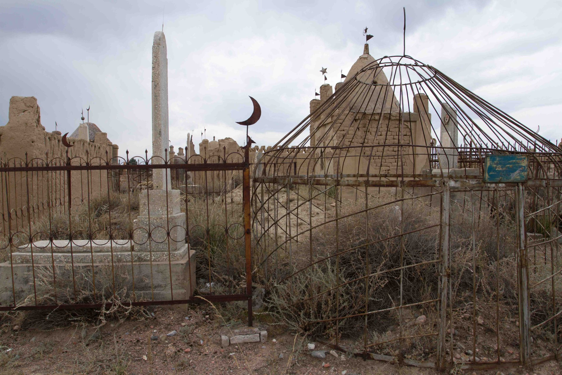 cemetery, Koshkor. some of the plots feature yurt shaped memorials that remind of giant bird cages.