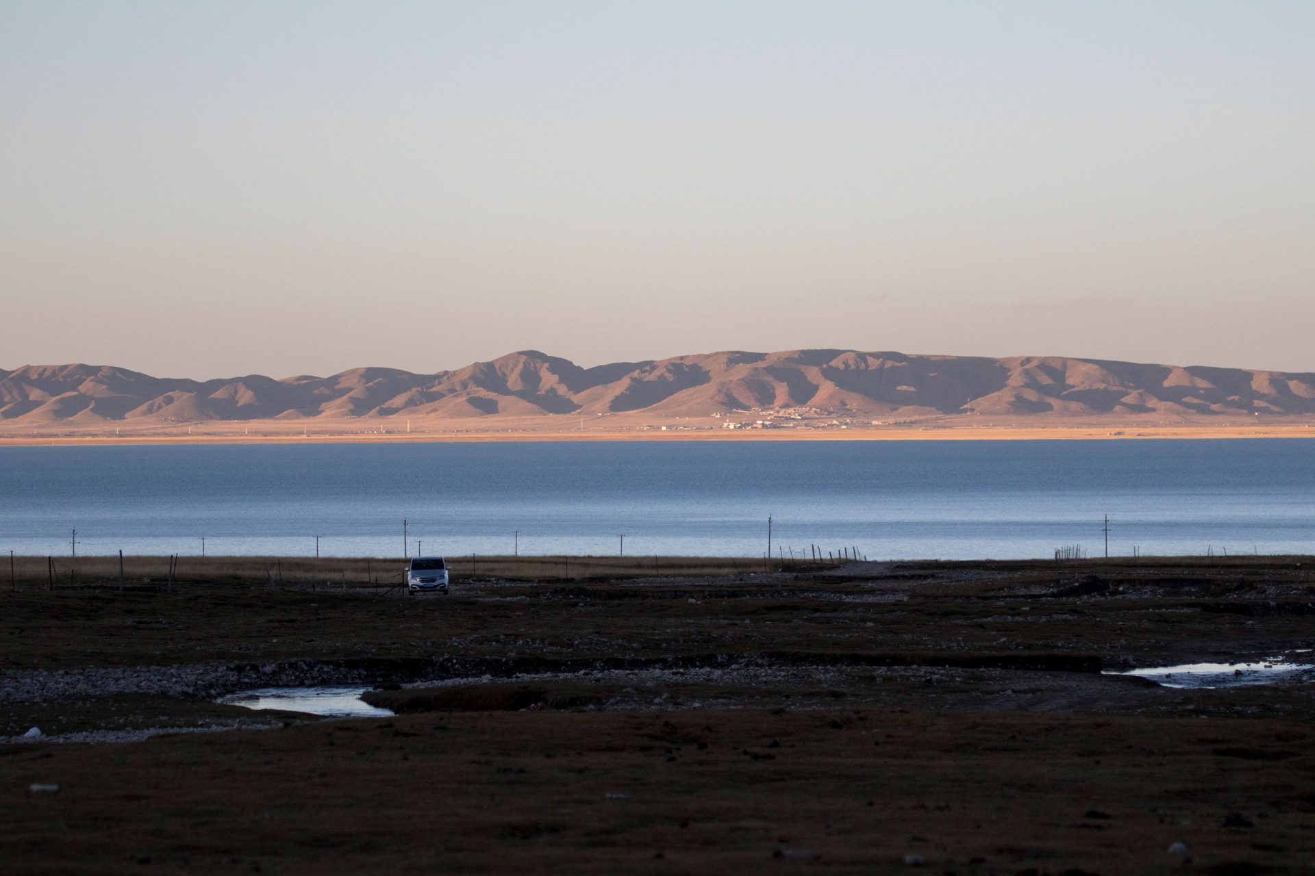 The valley in shadow with Qinghai Lake in the distance.